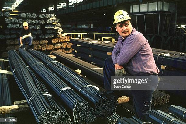 Workers take a break while moving finished steel at the Nova Hut steel mill, Ostrava, Czech Republic April 28, 1998.