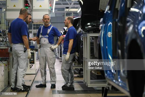 Workers take a brief break on the assembly line for Volkswagen Touareg Touran and TRoc models at the Volkswagen factory on March 01 2019 in Wolfsburg...