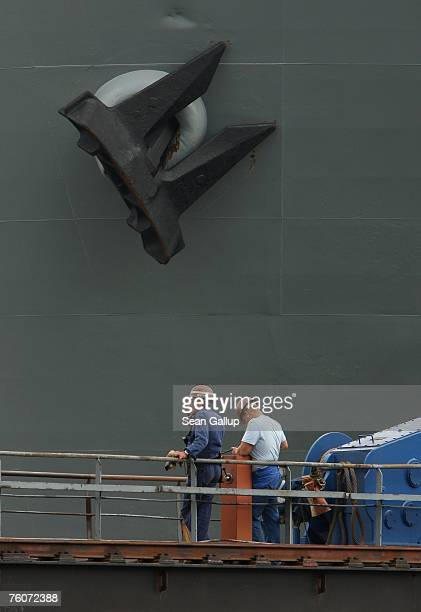Workers take a cigarette break while standing next to a ship and its anchor at the Blohm Voss shipyard August 13 2007 in Hamburg Germany Northern...
