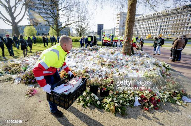 Workers take away flowers laid as a tribute near the scene of the attack on a tram at the 24 Oktoberplein in Utrecht on April 9, 2019. - Three people...