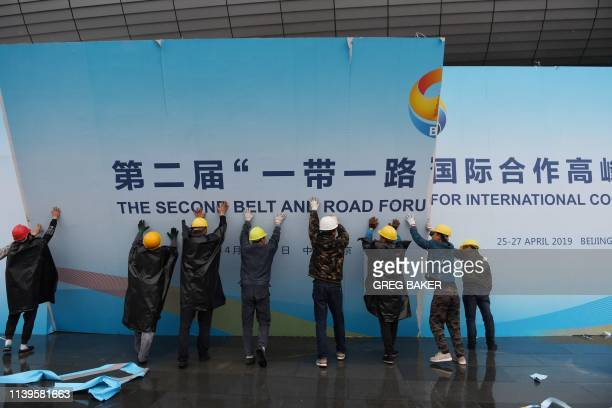 Workers take down a Belt and Road Forum panel outside the venue of the forum in Beijing on April 27 2019 Chinese President Xi Jinping urged dozens of...