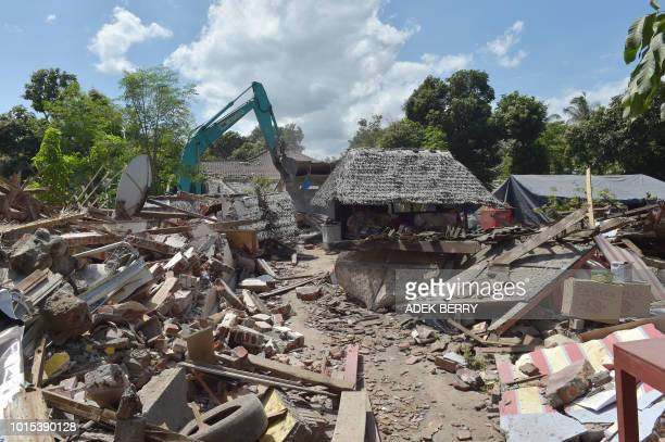 Workers take down a damaged shop with an excavator in an earthquakehit area in Gangga on August 12 2018 An earthquake on the Indonesian island of...