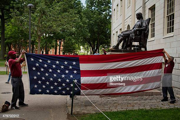 Workers take down an American flag next to a statue of John Harvard in Harvard Yard at the Harvard University campus in Cambridge Massachusetts US on...