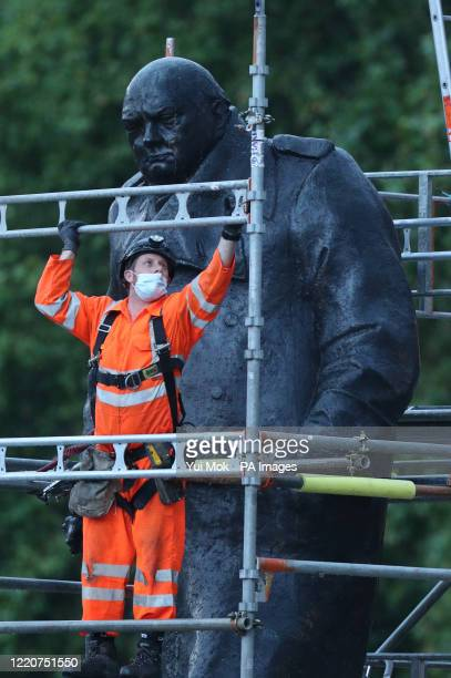 Workers take down the boarding and scaffolding around the Winston Churchill statue on Parliament Square, London.