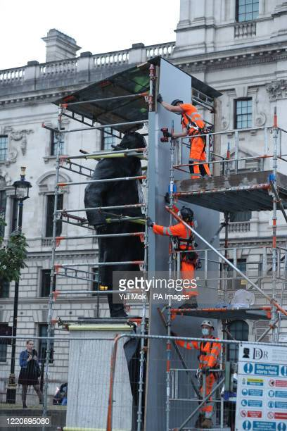 Workers take down the boarding around the Winston Churchill statue on Parliament Square, London.