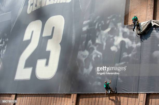 Workers take down the LeBron James banner from the Sherwin Williams building on the corner of Ontario and West Huron on July 3, 2018 in Cleveland,...