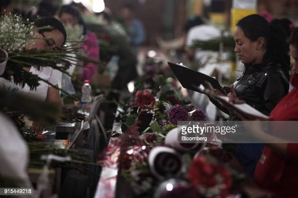 Workers take inventory of roses to be packed for export at a facility in the town of Cogua Cundinamarca department Colombia on Monday Feb 5 2018...