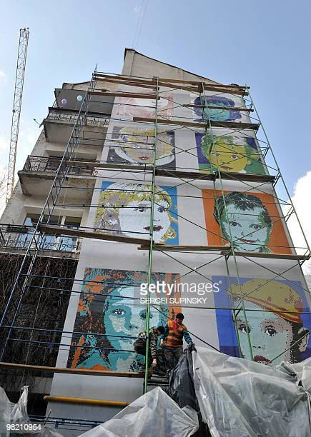Workers take off a covering from a mosaic panel made on a gable end of an apartment house in central Kiev on March 24 2010 during an artprotest...