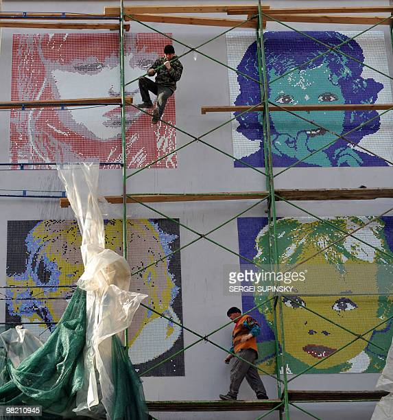 Workers take off a covering from mosaic panel made on a gable end of an apartment house in central Kiev on March 24 2010 during an artprotest action...
