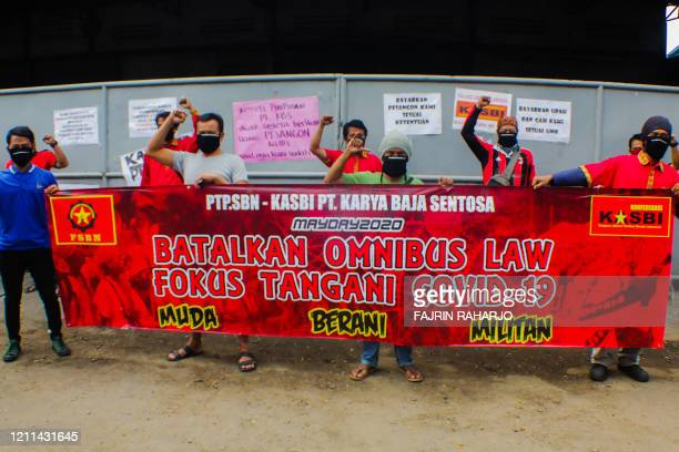 Workers take part in a protest on May Day or International Workers' Day in Tangerang Banten on May 1 to call on lawmakers to drop omnibus law...