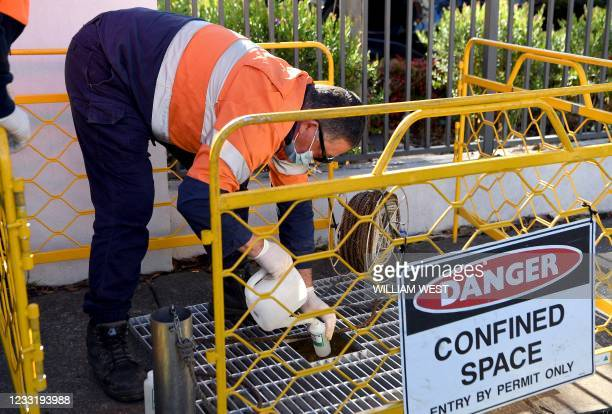 Workers take samples of water from a sewer to test for Covid-19 outside an aged care facility in the Melbourne suburb of Maidstone on May 31, 2021...