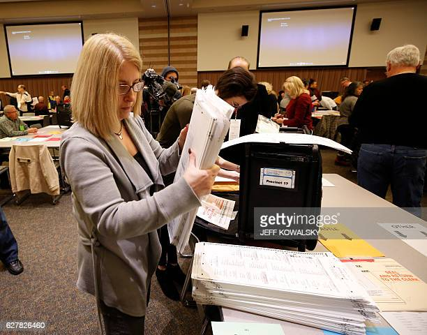 Workers take the ballots out of the containers before the start of the recount of ballots cast in Oakland County Michigan from the 2016 US...