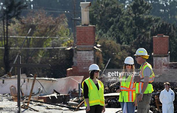 Workers talk as they stand next to burned homes near the epicenter of the gas line explosion that devastated a neighborhood near San Francisco...
