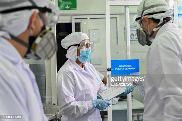 Workers talk at the cosmetics company Eurobelleza in Cali Colombiaon April 1 2020 during the coronavirus COVID19 pandemic Eurobelleza switched to the...