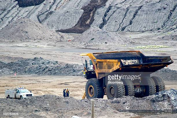Workers talk near a Caterpillar Inc mining truck at Syncrude Canada Ltd's oil sands North Mine in Fort McMurray Alberta Canada on Tuesday June 29...