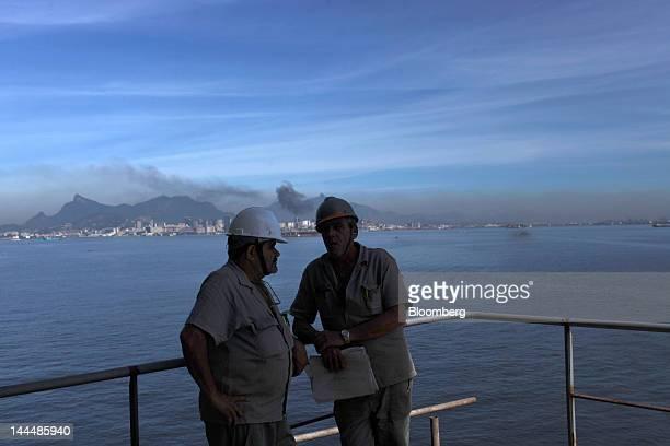 Workers talk on the deck of the Jose de Alencar vessel a Petroleo Brasileiro SA oil tanker under construction at the Maua SA shipyard in Niteroi...