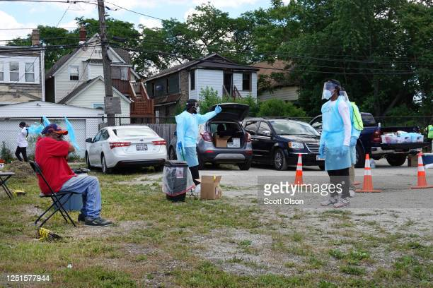 Workers talk residents through a COVID-19 self-test at a mobile COVID-19 testing site set up on a vacant lot in the Austin neighborhood on June 23,...