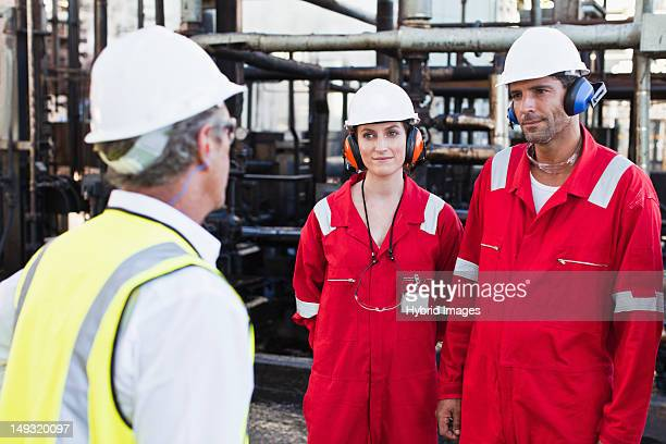 workers talking at chemical plant - hearing protection stock pictures, royalty-free photos & images