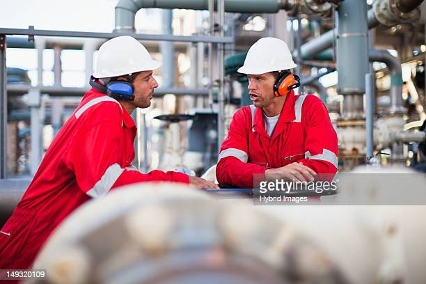 workers talking at chemical plant - oil industry stock pictures, royalty-free photos & images