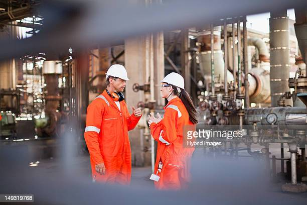 workers talking at oil refinery - protective workwear stock pictures, royalty-free photos & images