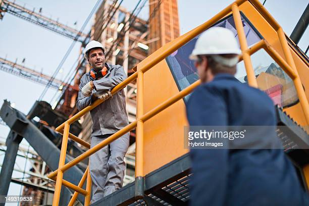workers talking at oil refinery - power occupation stock photos and pictures