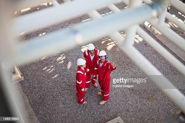 workers talking at oil refinery - gas refinery stock photos and pictures