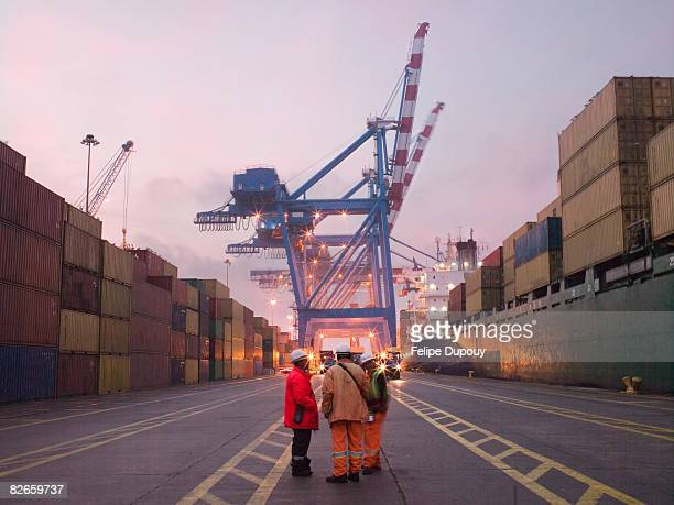 workers talking in a shipping yard - commercial dock stock pictures, royalty-free photos & images