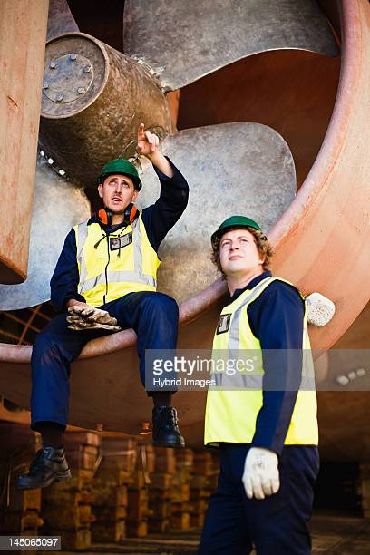 workers talking in propeller on dry dock - shipyard stock pictures, royalty-free photos & images