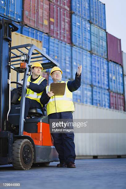 workers talking in shipping yard - hearing protection stock pictures, royalty-free photos & images