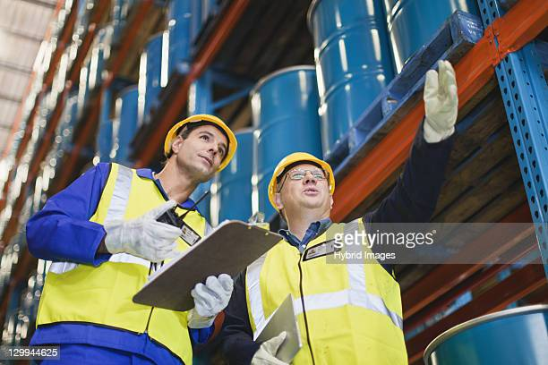 workers talking in warehouse - drum container stock photos and pictures