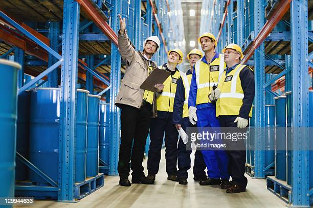 workers talking in warehouse - satisfaction stock pictures, royalty-free photos & images