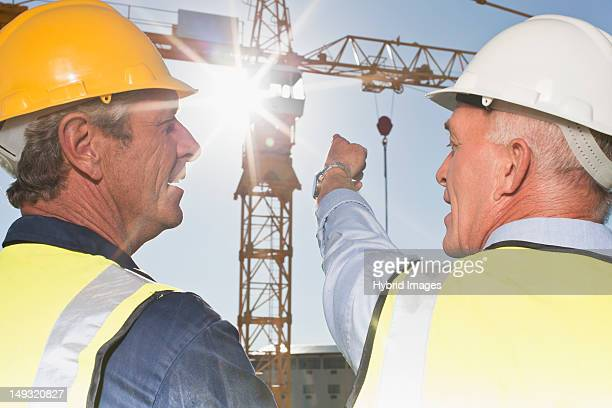 Workers talking on construction site