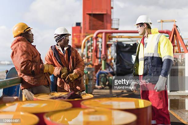 workers talking on oil rig - oil rig stock pictures, royalty-free photos & images