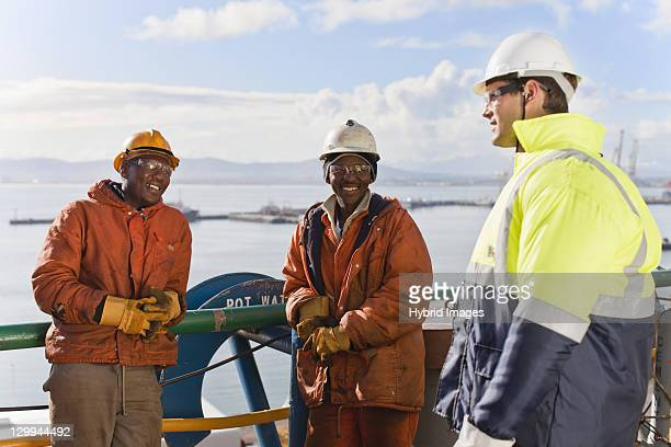 workers talking on oil rig - longshoremen stock pictures, royalty-free photos & images