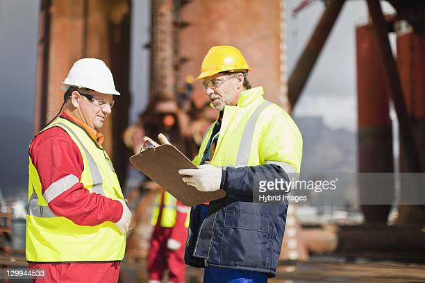 workers talking on oil rig - protective eyewear stock pictures, royalty-free photos & images