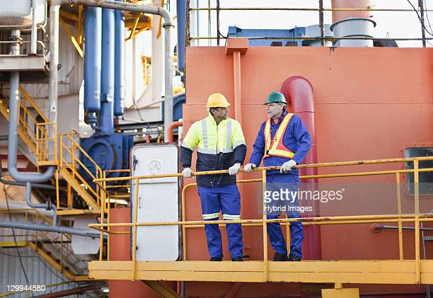 workers talking on oil rig - veiligheidshek stockfoto's en -beelden