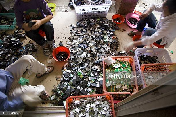 Workers tear apart mobile phones March 23 2008 in Guiyu China Since the late 1980's ewaste from developed countries has been imported to China and...