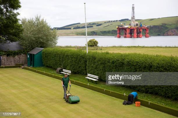 Workers tend to the grass at lawn bowls club in view of a mobile offshore drilling platform in this aerial view in Cromarty, U.K., on Tuesday, June...