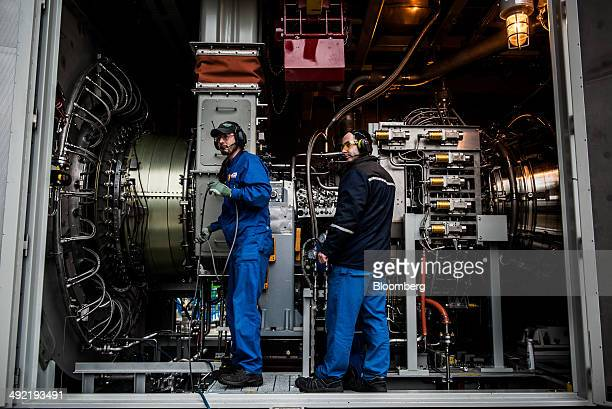 Workers test a turbine unit after assembly at the GE Power and Water plant operated by General Electric Co in Veresgyhaz Hungary on Thursday May 15...