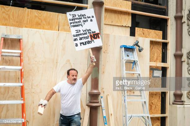 A workers that is in the middle of boarding up an Urban Outfitters store in SOHO to prevent any looting or other vandalism stops to bang on the board...