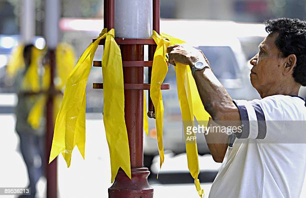 Workers tie yellow ribbons on posts along a street as sign of support for cancer striken former president Corazon Aquino in Manila on July 24 2009...