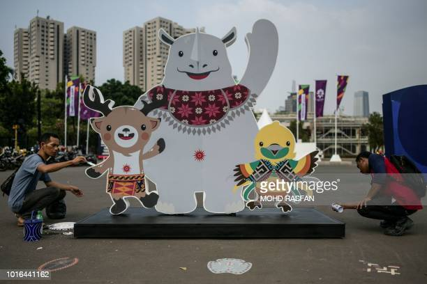 Workers touchup and spray paint an installation showing mascots Atung Kaka and Bhin Bhin ahead of the 2018 Asian Games in Jakarta on August 14 2018