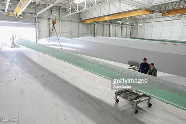 Workers transport a 45 meter long wind turbine blade at the Nordex wind turbine factory March 12 2007 in Roctock Germany Nordex has seen its sales...