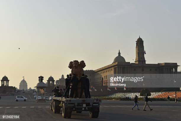 Workers transport a statue of the Indian national emblem Ashoka Stambha along Kings Boulevard near the the North Block of the Central Secretariat...