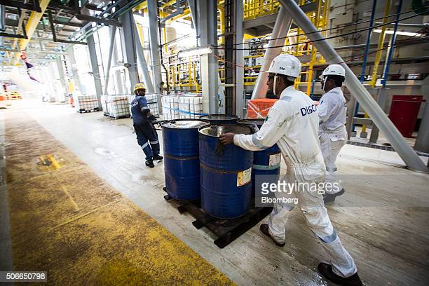 Workers transport oil drums on a pallet cart on the Tullow Oil Plc Prof John Evans Atta Mills Floating Production Storage and Offloading vessel...