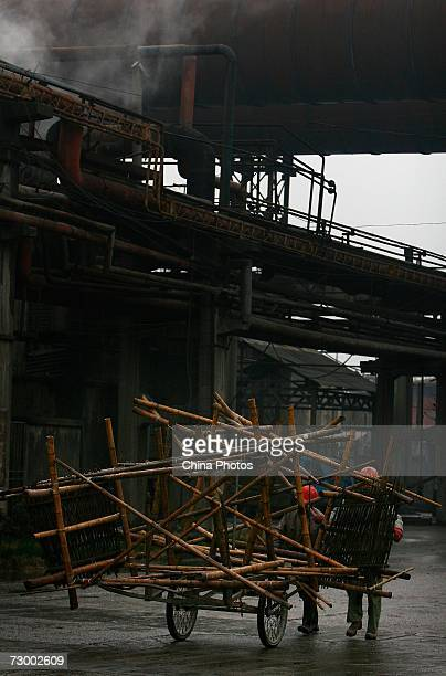 Workers transport scaffoldings at a Shanghai Baosteel Group factory January 15 2007 in Shanghai China According to state media Baosteel is preparing...