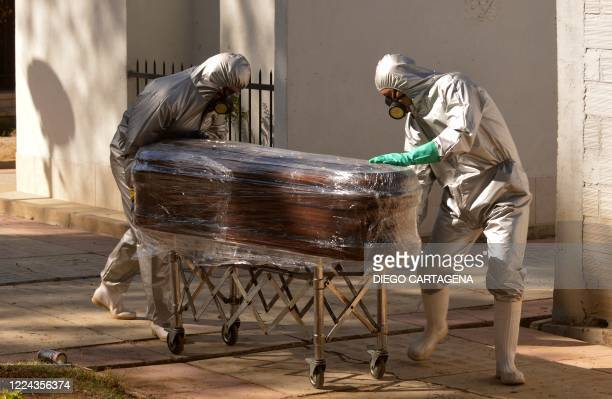 Workers transport the coffin of a COVID-19 victim to be buried in a common grave at the general cemetery in Cochabamba, Bolivia, on July 2, 2020.