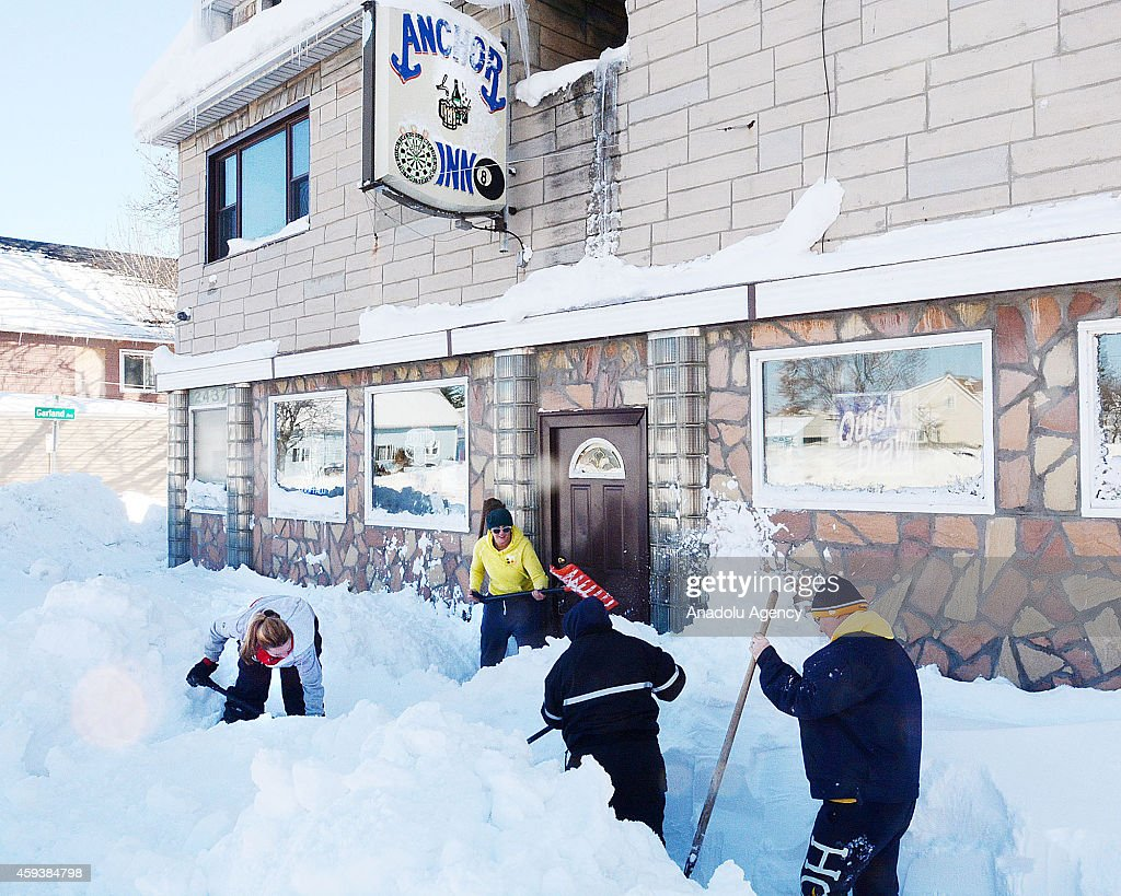 Workers try to clear snow in front of a building on November 21, 2014 in Buffalo, New York as the death toll attributed to Buffalo snow rises to 13. A brutal blast of Arctic air triggered a lake-effect storm and snow in the states of New York, Ohio, Michigan, Wisconsin and Pennsylvania.