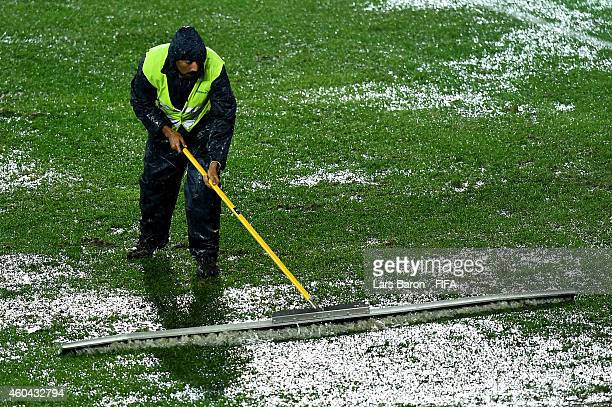 Workers try to dry out the pitch during the FIFA Club World Cup Quarter Final match between Cruz Azul FC and Western Sydney Wanderers FC at Prince...