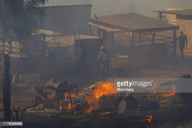 Workers try to extinguish smoldering embers on a ranch during the Easy Fire in Simi Valley California US on Wednesday Oct 30 2019 Officials in...